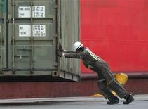 Imagen de archivo de un trabajador guiando un contenedor en el puerto de Valparaíso, Chile, nov 14 2005. La actividad económica de Chile anotó en el 2012 una expansión del 5,6 por ciento, apoyada en una sólida demanda interna, pero una esperada desaceleración en los próximos meses motivaría al Banco Central a mantener la cautela y dejar estable la tasa clave de interés. REUTERS/Eliseo Fernandez