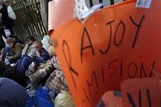"""Manifestantes se aglomeram diante da sede do Partido Popular, do premier Mariano Rajoy, segurando cartazes nos quais se lê """"Rajoy, demissão"""", em Madri. Os procedimentos tortuosos do sistema judicial espanhol, e uma oposição política fraca, significam que as alegações de corrupção não devem tirar o primeiro-ministro Mariano Rajoy do cargo. 04/02/2013 REUTERS/Susana Vera"""