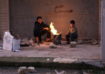 Boys warm up next to a fire outside a building in the Ain Tarma neighbourhood of Damascus February 5, 2013. REUTERS/Goran Tomasevic