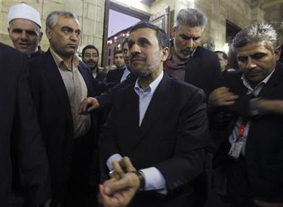 Iran's President Mahmoud Ahmadinejad (C) gestures in front of the shrine of Prophet Mohammed's grandson Hussein ibn Ali at the Al-Hussein mosque, named after the grandson, in old Cairo February 5, 2013. REUTERS/Amr Abdallah Dalsh