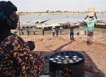 Los rebeldes tuareg que aspiran a la autonomía dentro de Mali dijeron el martes que han ocupado la localidad de Menaka, ampliando su control del remoto nordeste mientras se posicionan para dialogar con el Gobierno tras la retirada de los insurgentes vinculados a Al Qaeda. En la imagen, una mujer maliense mira a hombres cargando ayuda humanitaria en piraguas en Mopti, el 4 de febrero de 2013. REUTERS/Alain Amontchi