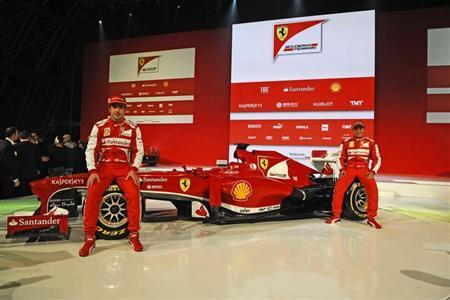 Ferrari Formula One driver Fernando Alonso (L) of Spain and Felipe Massa of Brasil pose near the new Ferrari F138 Formula One car is seen in this official undated handout image distributed by the Ferrari Press Office February 1, 2013. REUTERS/Ferrari Press Office/Handout
