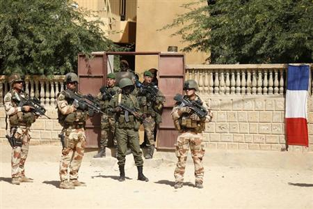 A Malian soldier (C, in helmet) patrols with French soldiers along the street outside the Ahmed Baba Institute, or Ahmed Baba Centre for Documentation and Research, in Timbuktu February 2, 2013. REUTERS/Benoit Tessier