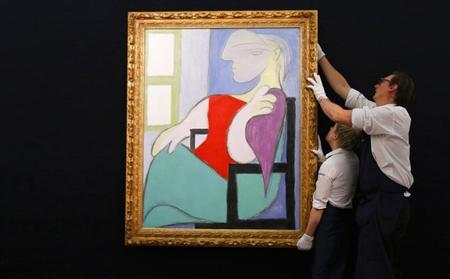 Sotheby's workers straighten ''Femme assise pres d'une fenetre'' from 1932 by Pablo Picasso, at Sotheby's in London January 31, 2013. REUTERS/Suzanne Plunkett