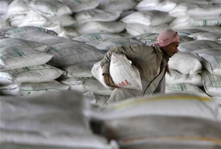 A labourer carries a cement bag before loading it onto a truck at a railway goods yard on the outskirts Ahmedabad June 1, 2012. REUTERS/Amit Dave/Files