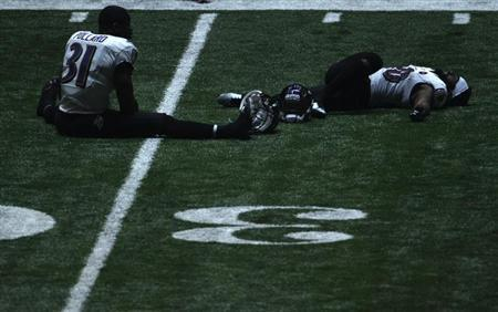 Baltimore Ravens strong safety Bernard Pollard (L) and free safety Ed Reed sit on the turf stretching during a power outage in the NFL Super Bowl XLVII football game against the San Francisco 49ers in New Orleans, Louisiana, February 3, 2013. REUTERS/Jonathan Bachman