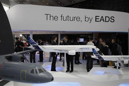 Visitors look at aircraft models at the EADS booth during the ILA Berlin Air Show in Selchow near Schoenefeld south of Berlin, September 13, 2012. REUTERS/Tobias Schwarz (GERMANY - Tags: TRANSPORT BUSINESS)