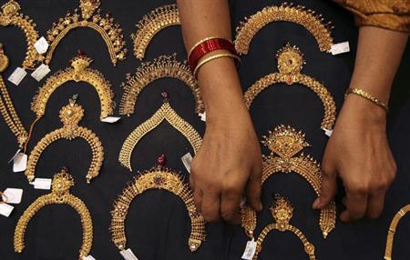 A woman checks a gold necklace inside a jewellery showroom in Hyderabad April 11, 2012. REUTERS/Krishnendu Halder/Files