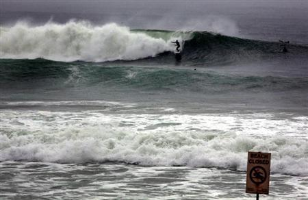 A surfer rides a wave behind a 'Closed Beach' sign on Manly Beach in Sydney February 2, 2013. Rough seas and high winds have caused the closure of many Sydney beaches over the past few days. REUTERS/David Gray (AUSTRALIA - Tags: ENVIRONMENT SOCIETY)