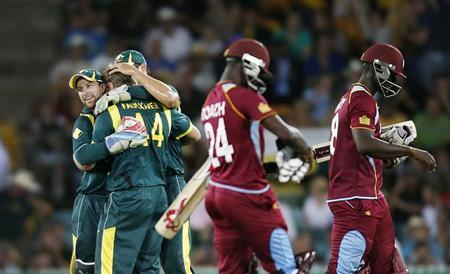 West Indies' Kemar Roach (C) and captain Darren Sammy (R) leave the field after losing their one-day international cricket match as Australia's Matthew Wade (L) hugs teammate James Faulkner, at Manuka Oval in Canberra February 6, 2013. REUTERS/Tim Wimborne