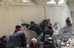 Combatente do Exército Sírio Livre dispara rifle por um buraco na parede de uma base militar síria durante confronto no bairro de Arabeen, em Damasco. Confrontos violentos aconteceram em Damasco nesta quarta-feira após uma ofensiva coordenada dos combatentes de oposição a partir dos subúrbios contra as forças do presidente Bashar al-Assad, encerrando um período de calma na capital. 03/02/2013 REUTERS/Goran Tomasevic
