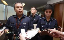 Superintendent Ho Yenn Dar (L), assistant director of media relations of Singapore Police Force listens to questions from journalists on the international match-fixing scam at the Ministry of Home Affairs in Singapore February 6, 2013. Singapore's police said on Tuesday it was helping its European counterparts investigate a syndicate accused of fixing the outcome of hundreds of soccer matches. REUTERS/Edgar Su