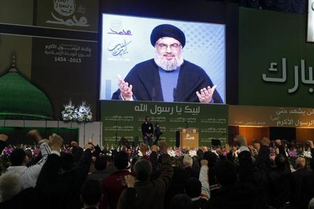 Lebanon's Hezbollah leader Sayyed Hassan Nasrallah addresses supporters from a screen during a rally to commemorate the birth of Prophet Mohammad in Beirut's suburbs, January 25, 2013. REUTERS/Sharif Karim/Files