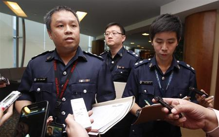 Superintendent Ho Yenn Dar (L), assistant director of media relations of Singapore Police Force listens to questions from journalists on the international match-fixing scam at the Ministry of Home Affairs in Singapore February 6, 2013. REUTERS/Edgar Su