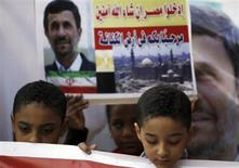 "Children stand in front of a sign and a poster of Iran's President Mahmoud Ahmadinejad in front of the Al-Hussein mosque, named after Prophet Mohammed's grandson Hussein ibn Ali, before Ahmadinejad's visit to the mosque in old Cairo February 5, 2013. Ahmadinejad was both kissed and scolded on Tuesday when he began the first visit to Egypt by an Iranian president since Tehran's 1979 Islamic revolution. The trip was meant to underline a thaw in relations since Egyptians elected an Islamist head of state, President Mohamed Mursi, last June. But it also highlighted deep theological and geopolitical differences. The sign reads, ""Enter Egypt, God willing, safe."" REUTERS/Amr Abdallah Dalsh (EGYPT - Tags: POLITICS RELIGION CIVIL UNREST)"