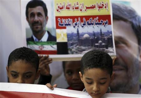 Children stand in front of a sign and a poster of Iran's President Mahmoud Ahmadinejad in front of the Al-Hussein mosque, named after Prophet Mohammed's grandson Hussein ibn Ali, before Ahmadinejad's visit to the mosque in old Cairo February 5, 2013. Ahmadinejad was both kissed and scolded on Tuesday when he began the first visit to Egypt by an Iranian president since Tehran's 1979 Islamic revolution. The trip was meant to underline a thaw in relations since Egyptians elected an Islamist head of state, President Mohamed Mursi, last June. But it also highlighted deep theological and geopolitical differences. The sign reads, ''Enter Egypt, God willing, safe.'' REUTERS/Amr Abdallah Dalsh (EGYPT - Tags: POLITICS RELIGION CIVIL UNREST)
