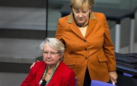 German Chancellor Angela Merkel (L) puts her hands on the shoulder of Education Minister Annette Schavan during a session of the Bundestag, the German lower house of parliament, in Berlin October 18, 2012. REUTERS/Thomas Peter