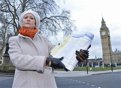 Julie Bailey, the founder of Cure The NHS, holds a copy of the report into the failings at mid-Staffordshire NHS Trust, outside the Houses of Parliament in London February 6, 2013. Bailey's mother died while at the hospital in 2007, local media reported. REUTERS/Toby Melville