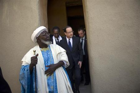 France's President Francois Hollande (C) flanked by Mali's interim president Dioncounda Traore (2ndL), visit the Djingareyber Mosque in Timbuktu during his one-day visit in Mali, February 2, 2013. French President Hollande flew to Mali on Saturday to support French troops fighting Islamist rebels in the Sahel nation and he visited the famed ancient city of Timbuktu that was recaptured from al Qaeda-allied fighters six days ago. REUTERS/Fred Dufour/Pool (MALI - Tags: POLITICS CONFLICT CIVIL UNREST)