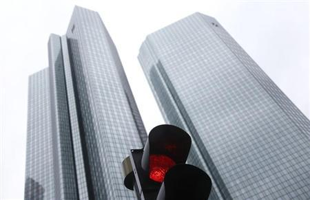 The headquarters of Germany's largest business bank, Deutsche Bank are seen behind a red traffic light in Frankfurt January 30, 2013. Deutsche Bank has appointed two internal executives to head its global commodities business as it restructures and cuts jobs, a source close to the bank said on Wednesday. Deutsche said last month its fourth-quarter profits would be affected by the restructuring aimed at achieving annual cost savings of 4.5 billion euros, but that there was no cause for alarm among investors. Deutsche Bank will announce its annual figures tomorrow. REUTERS/Kai Pfaffenbach (GERMANY - Tags: BUSINESS)