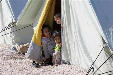 Syrian refugee children look from inside their tent in al-Marj in the Bekaa Valley December 27, 2012. REUTERS/Mohamed Azakir