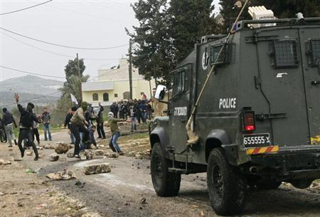 Palestinian protesters throw stones towards an Israeli police van during clashes with Israeli security officers at a weekly protest against the nearby Jewish settlement of Kdumim, in the West Bank village of Kfar Kadum, near Nablus February 1, 2013. REUTERS/Abed Omar Qusini