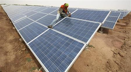A worker installs photovoltaic solar panels at the Gujarat solar park under construction in Charanka village in Patan district of Gujarat April 14, 2012. REUTERS/Amit Dave/Files
