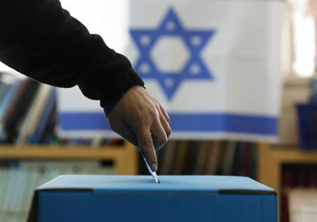 An Israeli flag is seen in the background as a man casts his ballot for the parliamentary election at a polling in the West Bank Jewish settlement of Ofra, north of Ramallah January 22, 2013. REUTERS/Baz Ratner