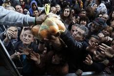 People reach out to take fruits and vegetables distributed for free by farmers during a protest against high production costs outside the Agriculture Ministry in Athens February 6, 2013. REUTERS/John Kolesidis