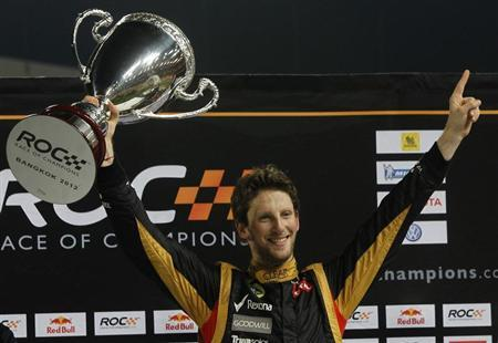 Driver Romain Grosjean from Team France holds up Race of Champions (ROC) trophy after winning over Tom Kristensen from Team All Stars at the Rajamangala National Stadium in Bangkok December 16, 2012. REUTERS/Chaiwat Subprasom