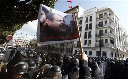 Tunisian protesters shout slogans during a demonstration after the death of Tunisian opposition leader Chokri Belaid (pictured on flag), outside the Interior ministry in Tunis February 6, 2013. REUTERS/Anis Mili