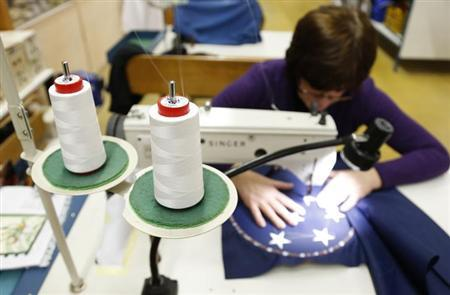 A worker sews stars on a U.S. national flag at the Waelkens flag company in Oostrozebeke February 4, 2013. REUTERS/Francois Lenoir