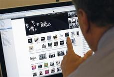 A man poses as he looks at music from the legendary band The Beatles on Apple's itunes music store website seen on an imac computer in New York, November 16, 2010. REUTERS/Mike Segar