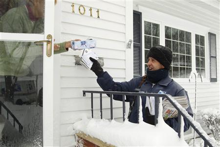 Mail carrier Mike Perkins delivers mail in the snow in Waterloo, Iowa in this file photo taken December 20, 2012. REUTERS/Matthew Putney/The Waterloo Courier/Handout