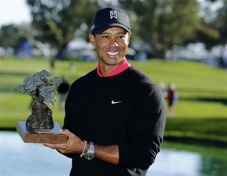 U.S. golfer Tiger Woods holds the trophy after winning the Farmers Insurance Open in San Diego, California January 28, 2013. REUTERS/Mike Blake