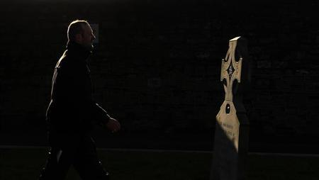 A man walks past a memorial to those who worked in the Magdalene Laundries, at Glasnevin Cemetery in Dublin February 6, 2013. REUTERS/Cathal McNaughton