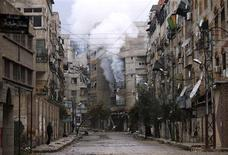 A man stands in an empty street near a burning building hit by a mortar shell fired by Syrian Army soldiers, in the Zamalka neighbourhood of Damascus February 6, 2013. REUTERS/Goran Tomasevic