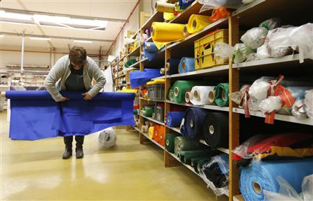 A worker rolls out blue fabric at the Waelkens flag company in Oostrozebeke February 4, 2013. REUTERS/Francois Lenoir