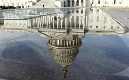 The dome of the Capitol is reflected in a puddle in Washington February 17, 2012. REUTERS/Kevin Lamarque