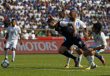 Clint Dempsey (L) of the U.S. is challenged by Honduras' Victor Bernardez (C) and Roger Espinoza during their 2014 World Cup qualifying soccer match at Olimpico stadium in San Pedro Sula February 6, 2013. REUTERS/Jorge Cabrera