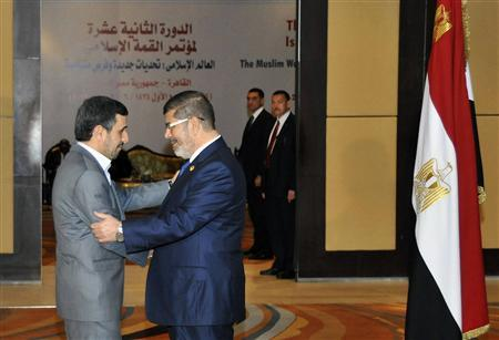 Egyptian President Mohamed Mursi (R) greets Iran's President Mahmoud Ahmadinejad before the opening of the Organisation of Islamic Cooperation (OIC) summit in Cairo February 6, 2013. REUTERS/Egyptian Presidency/Handout