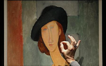 A staff member discusses ''Jeanne Hebuterne (au chapeau)'' from 1919 by Amedeo Modigliani, at Christie's auction house in London February 1, 2013. REUTERS/Suzanne Plunkett