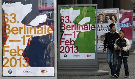 People walk in front of advertising banners for the upcoming 63rd Berlinale film festival in Berlin February 6, 2013. The Berlinale film festival runs from February 7 to 17 in the German capital. REUTERS/Fabrizio Bensch