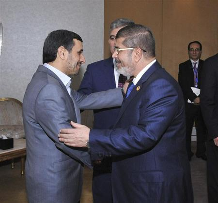 Egyptian President Mohamed Mursi (R) greets Iran's President Mahmoud Ahmadinejad as Turkish President Abdullah Gul look on before meeting at the Organisation of Islamic Cooperation (OIC) summit in Cairo February 6, 2013. REUTERS/Egyptian Presidency/Handout