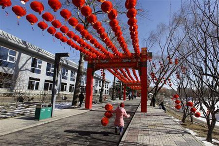 A girl holding red lanterns used for decoration runs in a park ahead of Chinese Lunar New Year celebrations in Beijing, February 6, 2013. REUTERS/Jason Lee
