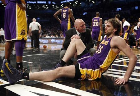 Los Angeles Lakers' Pau Gasol sits on the floor with a member of the Lakers medical staff after suffering an injury to his right leg in the fourth quarter of their NBA basketball game against the Brooklyn Nets in Brooklyn, New York, February 5, 2013. REUTERS/Mike Segar