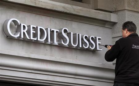 A worker uses a cordless screwdriver to fix the logo of Swiss bank Credit Suisse at a branch office in Zurich February 4, 2013. REUTERS/Arnd Wiegmann