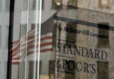 A U.S. flag is reflected in a window of the Standard and Poor's building in New York February 5, 2013. REUTERS/Brendan McDermid