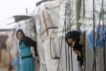 A Syrian refugee looks out of her tent in a refugee camp in the city of Tyre, in southern Lebanon January 31, 2013. REUTERS/Ali Hashisho