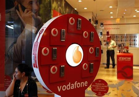 A woman talks on her mobile phone in front of a Vodafone store at Vodafone Turkey headquarters in Istanbul May 4, 2010. REUTERS/Murad Sezer/Files